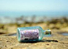 Gammal glasflaska med sedeln för euro 500 inom, makt av pengar Arkivbilder