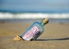 Gammal glasflaska med sedeln för euro 500 inom, sand av stranden Arkivfoton