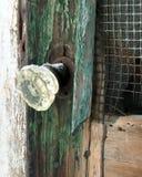 Gammal glass dörrknopp som täckas med snö på en förfallen gammal träskärmdörr Royaltyfri Fotografi