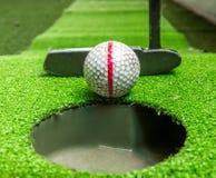 Gammal golfbollar och putter på konstgjort gräs Arkivfoto
