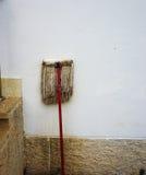 Gammal golvmopp på betongväggen royaltyfria foton