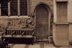 Gammal gotisk kyrklig dörr bricked upp och den närliggande bänken royaltyfria bilder