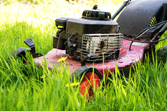 Gammal gräsklippare i högväxt gräs, eftersatt arbeta i trädgården royaltyfri fotografi