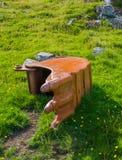 Gammal grävskopaskyffel som ligger i gräset Arkivbild