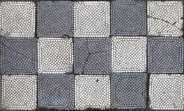 Gammal grå färg-vit tegelplatta på ett golv i schackbrädebeställning arkivbild
