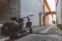 Gammal grå sparkcykel som parkeras i en smal gränd i Ascona royaltyfri bild
