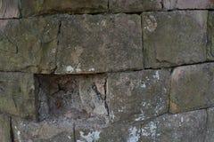 Gammal grå stenvägg med gropen Arkivfoton