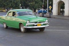 Gammal grön klassisk bilkörning förbi, havannacigarr, Kuba Arkivfoto