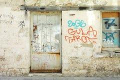 Gammal grafittivägg med det metalldörren och fönstret Royaltyfri Fotografi