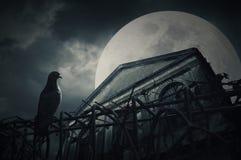 Gammal grungebyggnad på natten över molnig himmel och månen bakom Royaltyfri Fotografi
