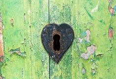 Gammal grungy grön dörr och rostat lås Arkivbild