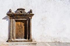 Gammal grungy kyrklig portal i en gata av den Marvao byn Royaltyfri Foto