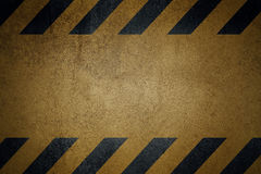 Gammal gul grungy yttersida för metallplatta med svarta varningsband Arkivbilder
