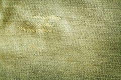 Gammal gul jeanstextur med skrapor Arkivbilder