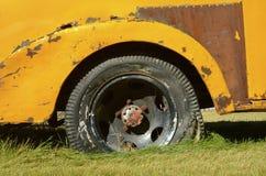 Gammal gul lastlastbil med det plana gummihjulet Royaltyfri Bild