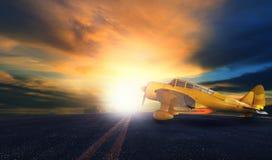 Gammal gul propellernivå på flygplatslandningsbana med solnedgånghimmelbac arkivfoton