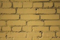 Gammal gul vägg av rektangulära tegelstenar med skada och skrapor Textur f?r grov yttersida arkivbild
