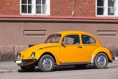 Gammal gul Volkswagen skalbagge i staden Royaltyfria Bilder