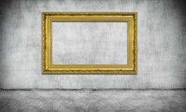 Gammal guld- ram på den gråa väggen royaltyfri foto