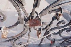 Gammal hänglås på ett dekorativt metallstaket Rysk brölloptradition som fäster hänglåset som ett symbol av förälskelse och lojali royaltyfri illustrationer