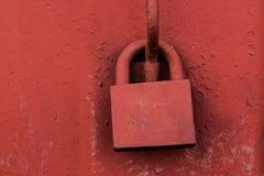 Gammal hänglås på röd dörr för metall Royaltyfri Foto