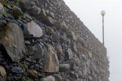 Gammal härlig stenvägg i regnigt väder Arkivfoto