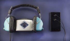 Gammal hörlurar och ljudsignal spelare, modern telefon med hörlurar, blå bakgrundsmusik royaltyfri bild