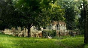 Gammal halva-förstörd byggnad i en parkera i en grön skog Royaltyfria Bilder