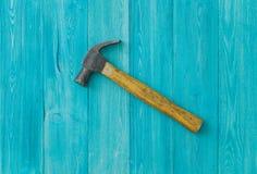 Gammal hammare på en blå träbakgrund royaltyfria bilder