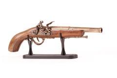 Gammal handeldvapen på en ställning, på en vit bakgrund Fotografering för Bildbyråer