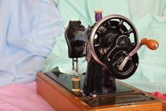 Gammal, handsymaskin med en visare, retro spolar av kulöra trådar och stycken av kulört bomullstyg Bakgrund för din de Arkivfoto
