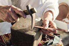 Gammal hantverkare som arbetar med hammaren på tunnbindarearmringen Arkivfoto