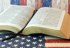 Gammal helig bibel och amerikanska flaggan Fotografering för Bildbyråer