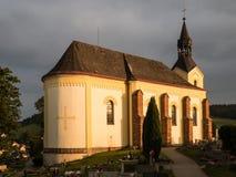 Gammal historisk kyrka och kyrkogård i en liten stad i tjecken Arkivfoto