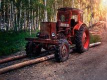Gammal hjultraktor i träna arkivbild