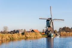 Gammal holländsk väderkvarn på kanten av en liten flod Royaltyfria Bilder
