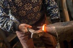 Gammal hovslagare som förfalskar manuellt smält metall med hammaren på städet royaltyfria foton