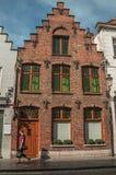 Gammal hus och gångare för tegelsten i Bruges Fotografering för Bildbyråer