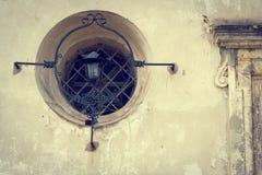Gammal husbakgrund: lykta och rundafönster på väggen Fotografering för Bildbyråer