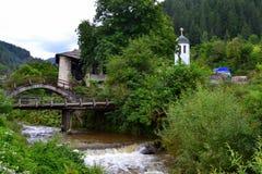 Gammal husbro och kyrka royaltyfri fotografi