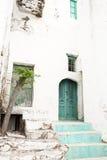 Gammal husfasad med den gröna trädörren som ser som en fördärva Royaltyfri Foto