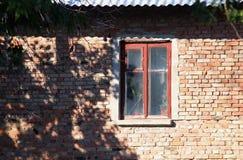 Gammal husvägg för röd tegelsten med fönstret Begrepp av den gamla staden Royaltyfria Foton