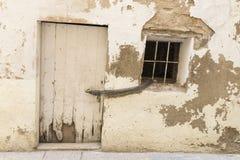 Gammal husvägg med den vita dörren och fönstret Arkivfoton