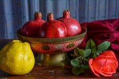 Gammal indisk vas med frukt och en scharlakansrött ros Fotografering för Bildbyråer