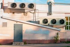 Gammal industribyggnad med industriellt kyla fläktar på väggen royaltyfri bild