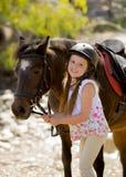 Gammal innehavtygel för ung flicka 7 eller 8 år av den lilla ponnyhästen som ler den lyckliga bärande säkerhetsjockeyhjälmen i so Fotografering för Bildbyråer