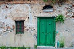 Gammal italiensk stenhusfasad med den gröna dörren Arkivfoto