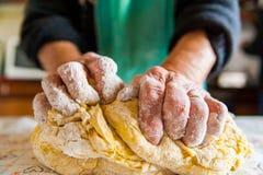 Gammal italienska dams händer som förbereder hem gjord italiensk pasta Arkivfoto