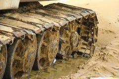 Gammal järnlarv i våt sand Rostiga stålhjul och larvband av en stor bulldozer, behållare, grävskopa, i fuktig sand och Royaltyfria Foton
