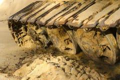 Gammal järnlarv i våt sand Rostiga stålhjul och larvband av en stor bulldozer, behållare, grävskopa, i fuktig sand och Arkivfoto